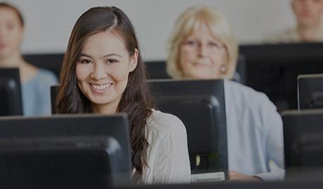 Photo de deux femmes souriantes devant des écrans d'ordinateur.