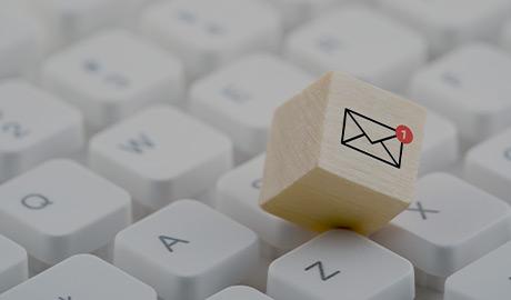 Gros plan sur un clavier d'ordinateur avec un dé en bois dont la face visible représente l'illustration d'une enveloppe.