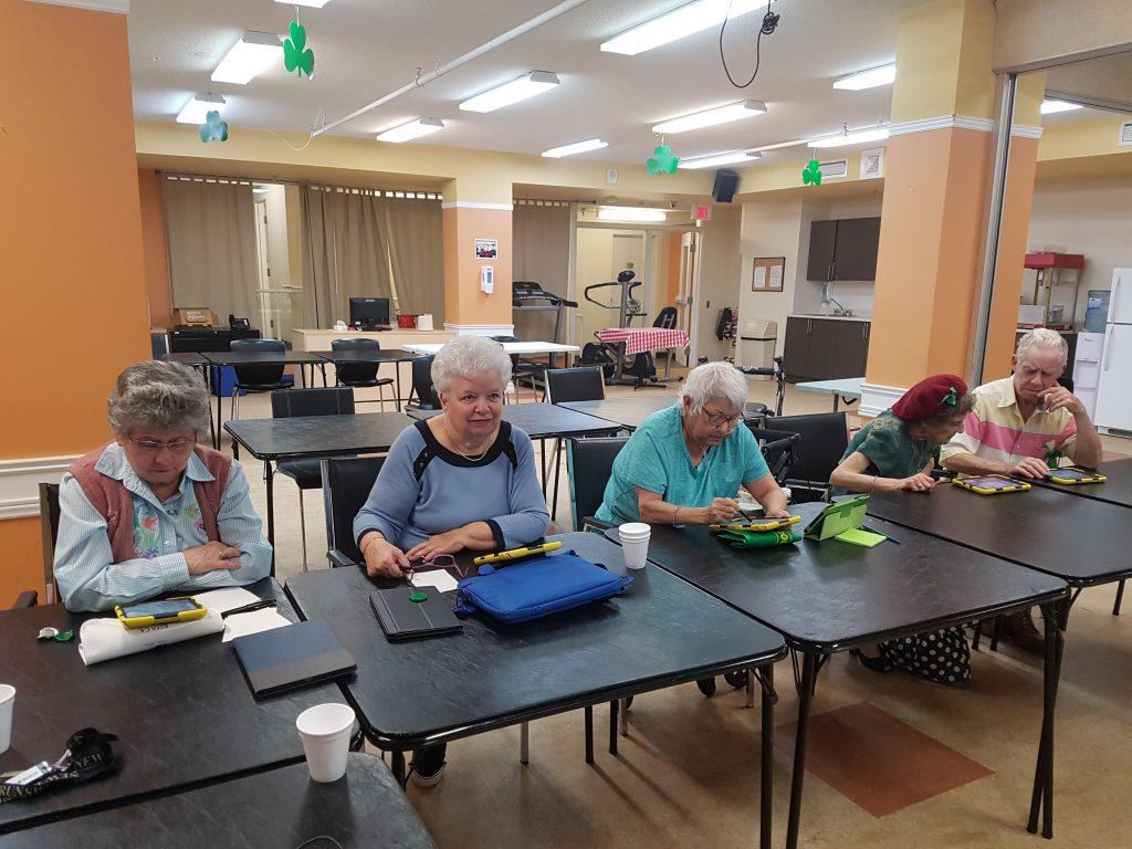 Photo de personnes aînées assises à des tables avec des tablettes numériques