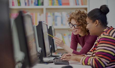 AlphaNumerique : Photo de deux femmes devant un écran d'ordinateur.