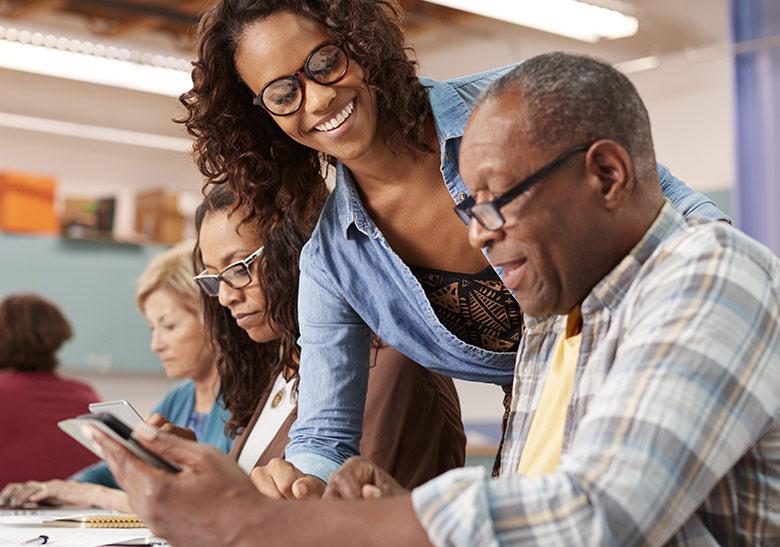 Photos de quatre personnes apprenant à se servir d'une tablette numérique.