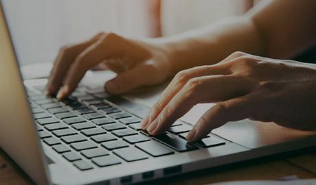 AlphaNumerique : Photo d'un clavier d'ordinateur portable avec mains tapant dessus.